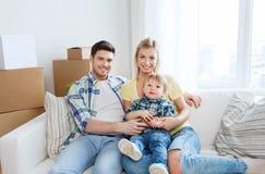 Glückliche Familie mit den Kästen, die auf neues Haus sich bewegen Stockfoto