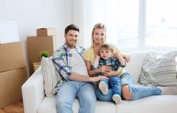 Glückliche Familie mit den Kästen, die auf neues Haus sich bewegen Lizenzfreies Stockfoto