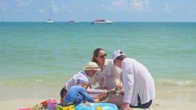 Glückliche Familie mit den Kindern, die auf dem sandigen Strand mit Spielwaren spielen Tropeninsel, an einem heißen Tag Lizenzfreie Stockbilder