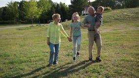 Glückliche Familie mit den Kindern, die Spaß im Park haben stock video footage