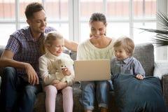 Glückliche Familie mit den Kindern, die Spaß unter Verwendung des Laptops auf Sofa haben stockbilder