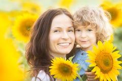 Glückliche Familie auf dem Sonnenblumegebiet Stockfotografie