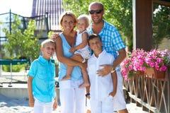 Glückliche Familie mit drei Kindern, die zusammen stehen Stockfotografie