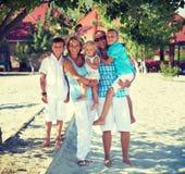 Glückliche Familie mit drei Kindern, die zusammen stehen Stockbilder