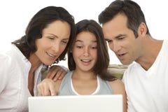 Glückliche Familie mit einem Kind, das Laptop verwendet Stockfotos