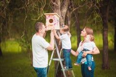 Glückliche Familie mit hölzernem Vogelhaus Stockfotografie