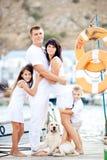 Glückliche Familie mit Hund auf Anlegeplatz am Sommer Lizenzfreies Stockfoto