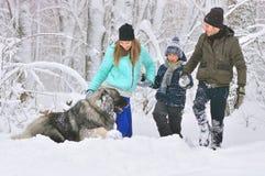 Glückliche Familie mit Hund draußen in einer Winterwaldmutter, in einem fother, in einem Sohn und in einem großen Schoßhund stockfotografie