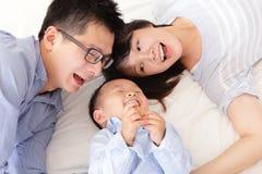 Glückliche Familie mit Kindern im Bett Stockfotografie