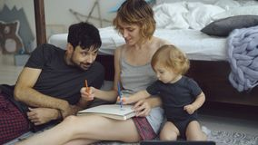 Glückliche Familie mit netter entzückender Tochterzeichnung im Album mit den Bleistiften, die zu Hause nahe Bett sitzen Lizenzfreie Stockfotos