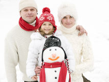 Glückliche Familie mit Schneemann Stockfotografie