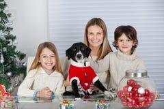 Glückliche Familie mit Schoßhund während des Weihnachten Stockfotos