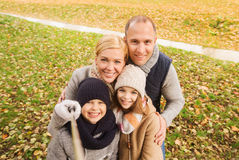 Glückliche Familie mit selfie Stock im Herbstpark Lizenzfreie Stockfotos