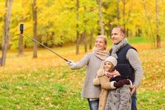 Glückliche Familie mit Smartphone und monopod im Park Lizenzfreies Stockbild