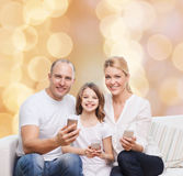 Glückliche Familie mit Smartphones Stockfotos