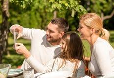 Glückliche Familie mit Tabletten-PC draußen Lizenzfreie Stockfotografie