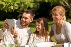 Glückliche Familie mit Tabletten-PC draußen Stockbild