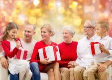Glückliche Familie mit Weihnachtsgeschenken über Lichtern Lizenzfreie Stockbilder