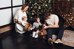 Glückliche Familie mit Weihnachtsgeschenken an verziertem Tannenbaum lizenzfreie stockfotos