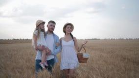 Glückliche Familie mit wenigem Kindermädchen, das auf gelbe Weizenährchen auf dem Herbstgebiet mit Brot in einem Korb spricht und stock video footage