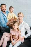 glückliche Familie mit zwei entzückenden Kindern, die an der Kamera lächeln lizenzfreie stockfotografie