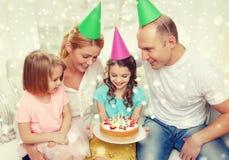 Glückliche Familie mit zwei Kindern in den Parteihüten zu Hause Lizenzfreies Stockbild