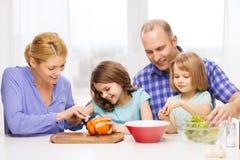 Glückliche Familie mit zwei Kindern, die zu Hause Abendessen machen Lizenzfreies Stockfoto