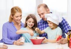 Glückliche Familie mit zwei Kindern, die zu Hause essen lizenzfreie stockfotografie