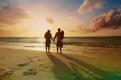 Glückliche Familie mit zwei Kindern gehen auf Sonnenuntergangstrand Stockfotos