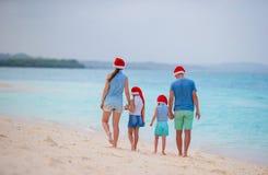 Glückliche Familie mit zwei Kindern in Santa Hats auf Sommerferien Weihnachtsfeiertage mit dem jungen Genießen der vierköpfigen F stockbild