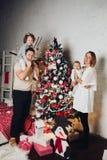 Glückliche Familie mit zwei Kindern am Weihnachtsbaum stockfotografie