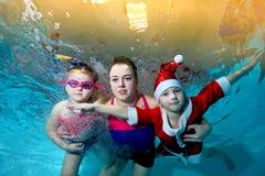 Glückliche Familie - Mutter, Tochter und Sohn in einer roten Klage Santa Claus schwimmen unter Wasser im Pool und betrachten mich stockbilder