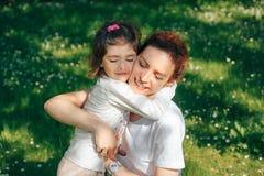 Glückliche Familie, Mutter umarmt ihre Tochter Stockbild