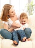 Glückliche Familie. Mutter- und Babytochter auf dem Sofa Stockfotos