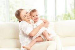 Glückliche Familie. Mutter- und Babytochterspiele, Umarmen, küssend Stockfoto