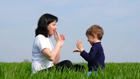 Glückliche Familie: Mutter und Kind sitzen auf grünem Gras und dem Spiel und schlagen sich auf beklopptem stock footage