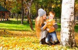 Glückliche Familie: Mutter und Kindsonr haben Spaß im Herbst auf Herbstpark Junges Mutter- und Kindermädchen, das in den Blättern lizenzfreie stockbilder