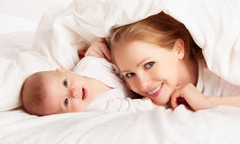 Glückliche Familie. Mutter und Schätzchen, die unter Decke spielen stockfotografie
