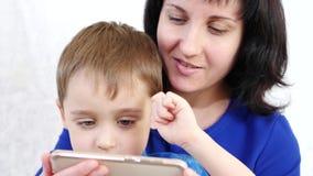 Glückliche Familie: Mutter und Sohn halten einen Smartphone und spielen mit der Anwendung für Kinder im Internet stock video