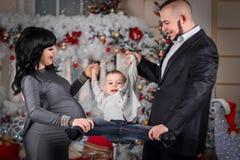 Glückliche Familie Mutter und Vati rollten seinen Sohn zu Händen von Weihnachten lizenzfreie stockfotos