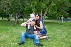 Glückliche Familie: Mutter-, Vater- und Tochterbaby im Park Stockfoto