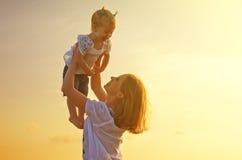 Glückliche Familie Mutter wirft oben Baby im Himmel bei Sonnenuntergang Stockfotos