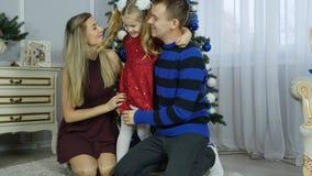 Glückliche Familie nahe Weihnachtsbaum glücklicher Muttervati und -tochter, die nahe Weihnachtsbaum umarmt und küsst stock video