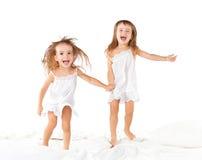 Glückliche Familie scherzt die Zwillingsschwestern, die auf das Bett springen, das Spielen Stockbilder