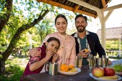 Glückliche Familie sitzen durch die Tabelle im Park Platten mit verschiedenen Früchten und Gläsern mit Wasser sind auf dem Tisch stockbilder