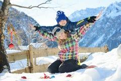 Glückliche Familie spielt draußen in einem alpinen Dorf Stockfotos