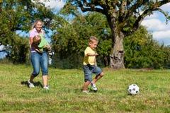 Glückliche Familie spielt Fußball am Sommer lizenzfreie stockfotos