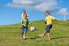 Glückliche Familie spielt Fußball am Sommer lizenzfreies stockbild