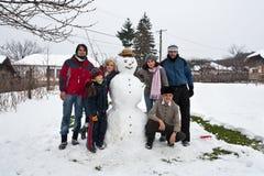 Glückliche Familie um einen Schneemann Stockbild