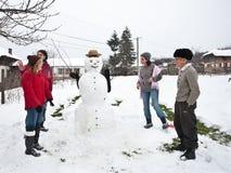 Glückliche Familie um einen Schneemann Stockfotos